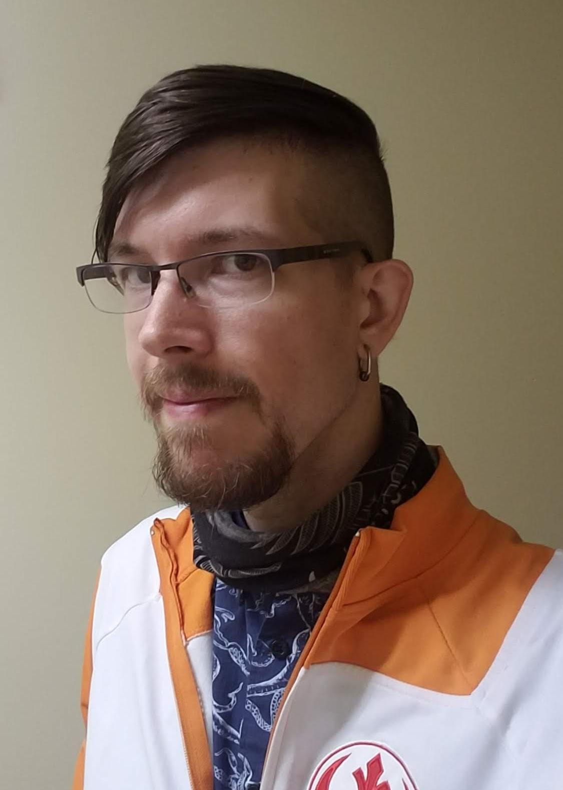 Image of the host wearing half-framed rectangular glasses, a blue shirt, and an orange Rebel Alliance jacket.