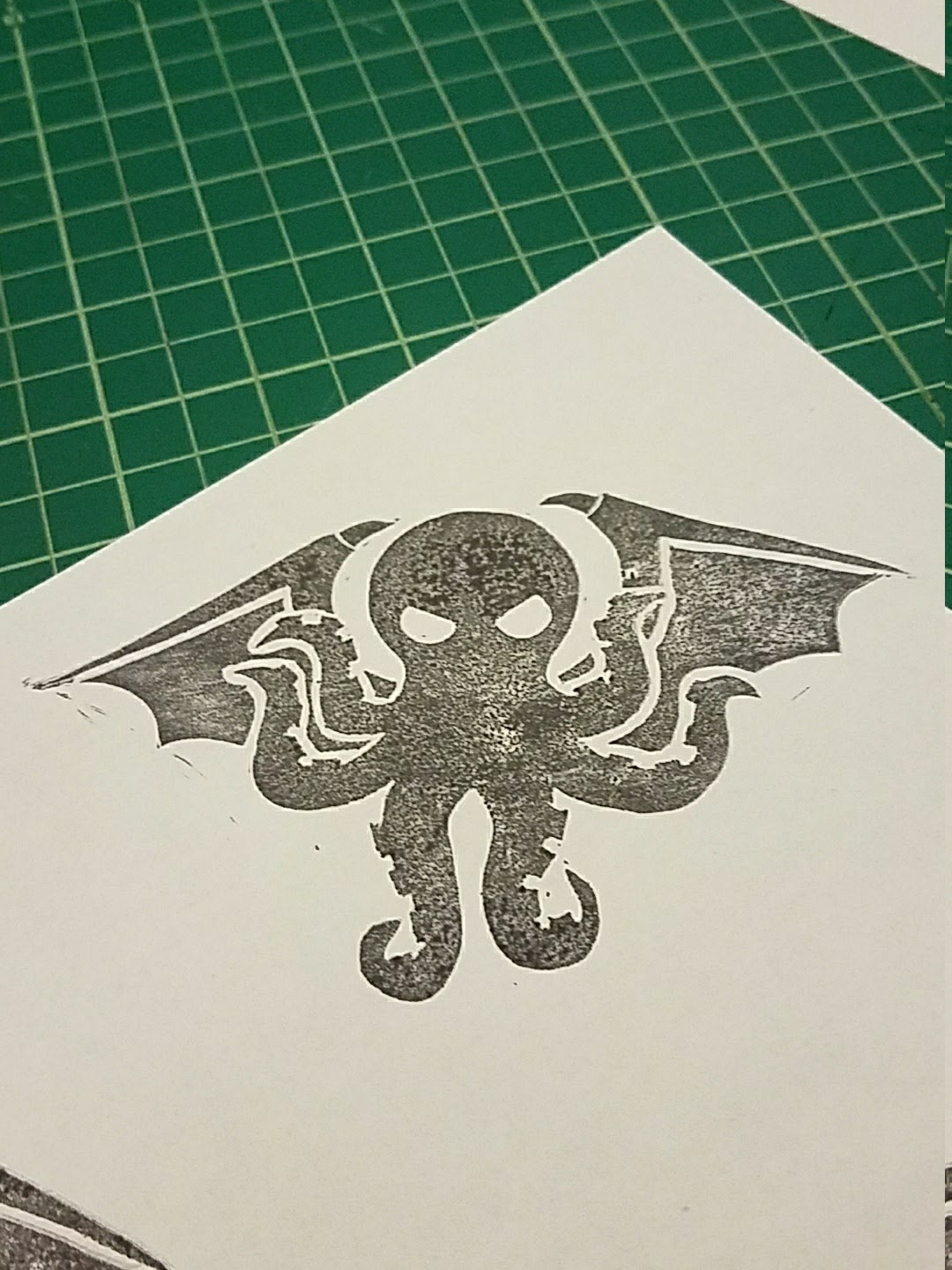 A block-printed image of Cthulhu's head and wings in a mottled black on a corner of a piece of white paper. The paper is resting on a gridded green cutting mat.